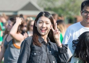 student showing peace sign